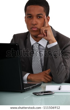 businessman at his desk thinking - stock photo
