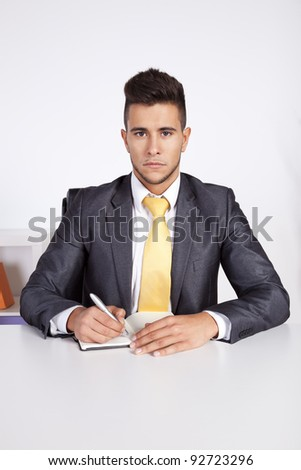 Businessman at his office taking some notes in his agenda - stock photo