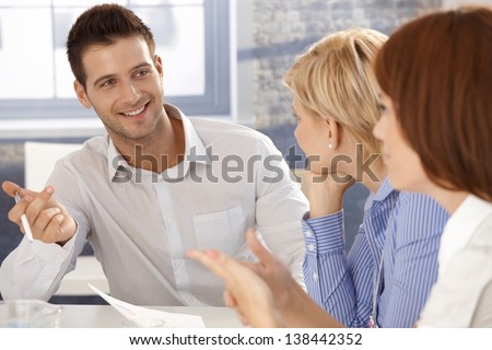 Businessman at meeting, smiling, talking to colleagues. - stock photo