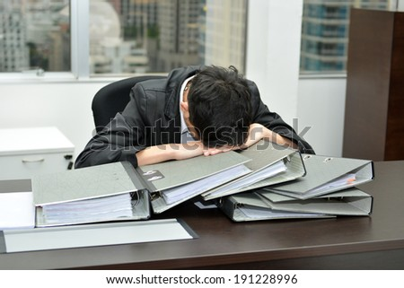 businessman at office desk overloaded with work. - stock photo