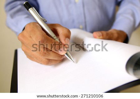 Businessman at office desk signing a contract. signature