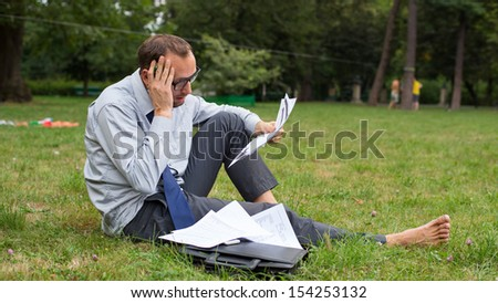 Businessman at the park with notes. - stock photo