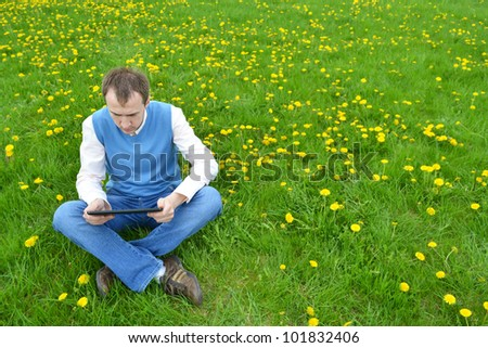 Businessman at the park with tablet. - stock photo