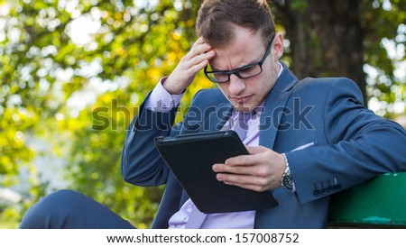 Businessman at the park with tablet sitting on a bench. - stock photo