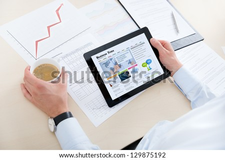 Businessman at the workplace drinking coffee and looking latest business news on modern digital computer. - stock photo