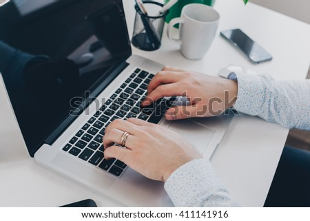Businessman at work. Close-up top view of man working on laptop