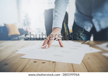 Businessman at work. Holding pencil in his hand. Architectural project on table. Blurred background, horizontal mockup. - stock photo