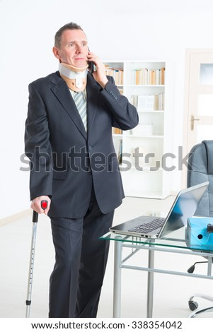 Businessman at work wearing neck brace with crutches - stock photo