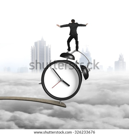 Businessman balancing alarm clock on edge of wooden plank, with cloudy cityscape background. - stock photo