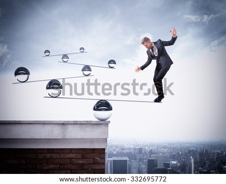 Businessman balancing on boards with iron balls - stock photo