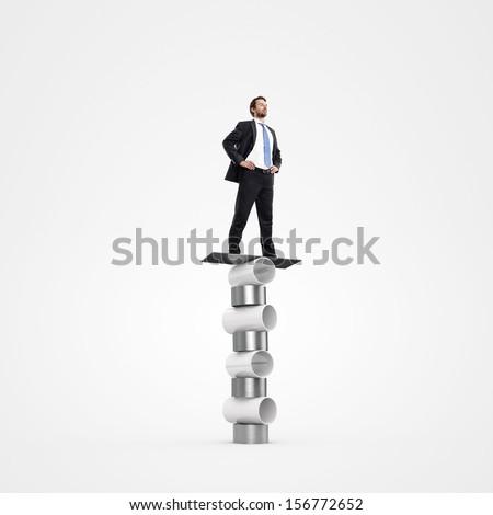 businessman balancing on circus cylinders - stock photo