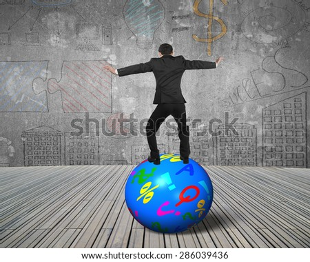 Businessman balancing on the colorful symbols ball, with business concepts doodles indoors background. - stock photo