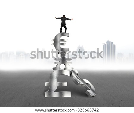 Businessman balancing on top of stack money symbols, with gray city buildings skyline background.
