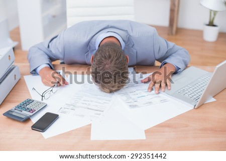 Businessman being depressed by accounting in his office - stock photo