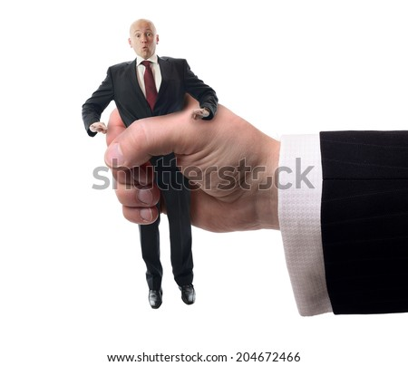 Businessman being squashed in a hand isolated on a white background, concept of problems at work. - stock photo