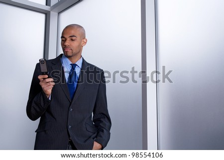 Businessman beside an office window, dialing a number on his cell phone. - stock photo