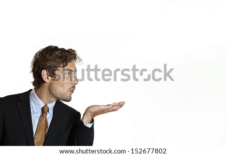 Businessman blowing idea from his hand - stock photo