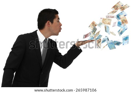 Businessman blowing money out of his hand throwing it away or waisting it.