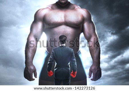 businessman boxing against a big muscular man - stock photo