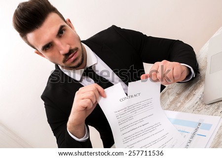 Businessman breaking a Contract at the office  - stock photo