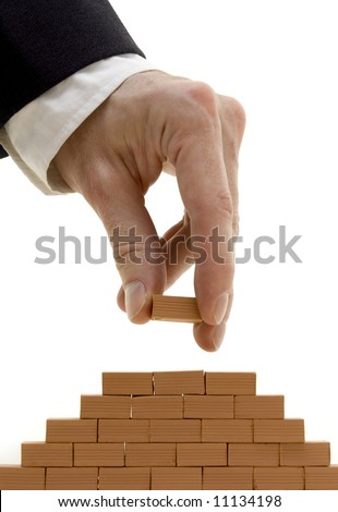 businessman building a bricks wall pyramid isolated on white - stock photo