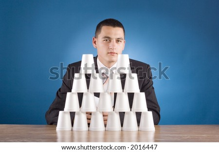 businessman building cups' pyramid (blue background) - stock photo