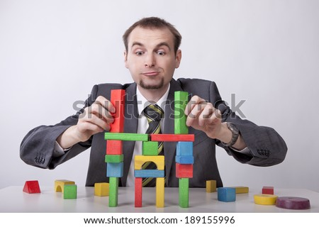 Businessman builds castle from toy's  blocks - stock photo