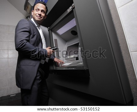Businessman by an atm machine