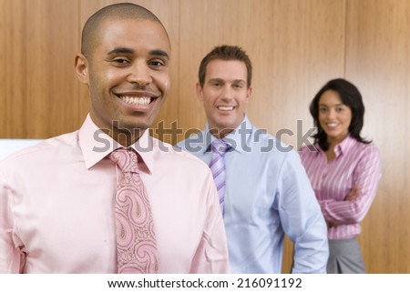 Businessman by two colleagues, smiling, portrait, close-up - stock photo