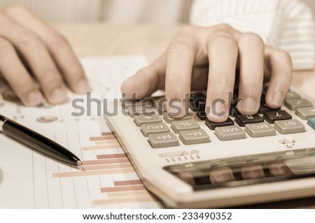 Businessman calculate on the desk in office. - stock photo