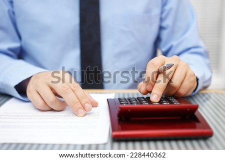 Businessman calculating  and checking articles of agreement - stock photo