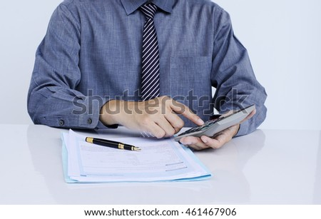 Businessman calculating at office desk
