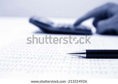 businessman calculating expense at desk in office - stock photo