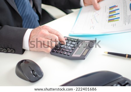 Businessman calculating financial results at the office - stock photo