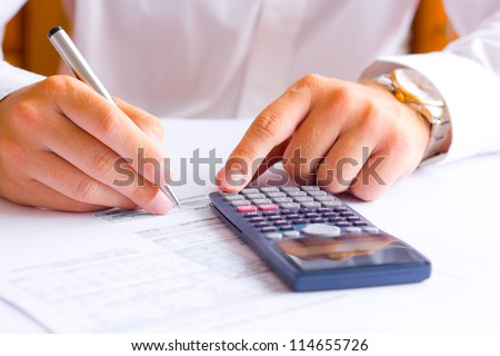 Businessman calculating financial results in the office - stock photo