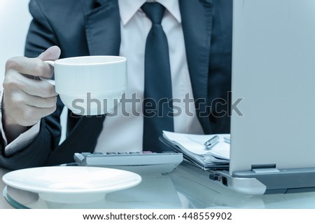 Businessman calculating the information with laptop and holding the coffee cup, business concept, cool tone white balance