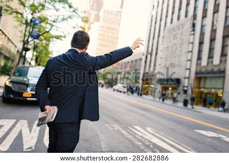 Businessman calling a taxi in Manhattan on the street. New York City. - stock photo