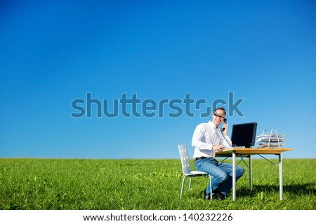Businessman calling using telephone on his table in green meadow - stock photo