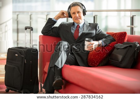 Businessman calm and relaxed enjoys music and coffee at the airport - stock photo