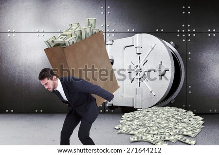 Businessman carrying bag of dollars against digitally generated opened safe - stock photo