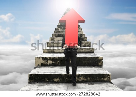 Businessman carrying big 3D red arrow sign and climbing on old dirty concrete stairs with sky cloudscape sunlight background - stock photo