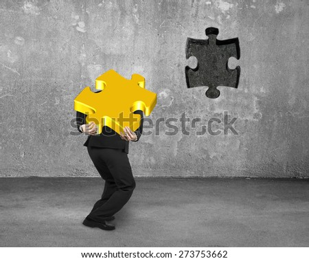 Businessman carrying 3D gold jigsaw puzzle piece to insert the dark hole on concrete wall background - stock photo