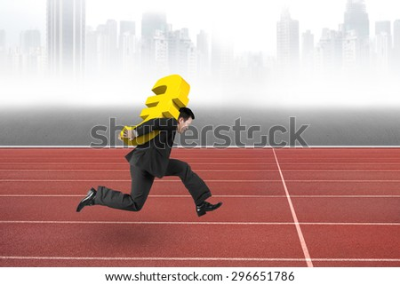 Businessman carrying 3D golden euro sign running on red track, with gray city skyline background.