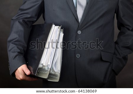 Businessman carrying file folders - stock photo