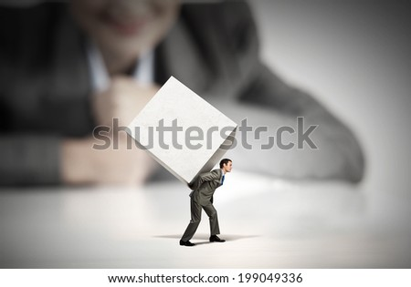 Businessman carrying white blank cube on back - stock photo