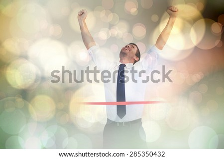 Businessman celebrating success with arms up against yellow abstract light spot design - stock photo