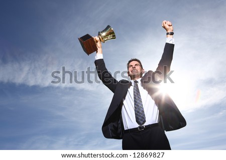 Businessman celebrating with trophy - stock photo
