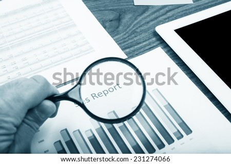 Businessman checking a graph with a magnifying glass, closeup - stock photo