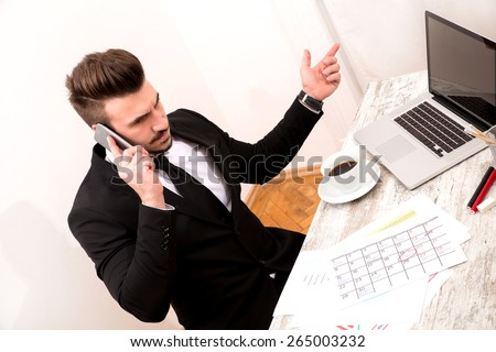 Businessman checking appointments in the calendar at the office and talking by phone