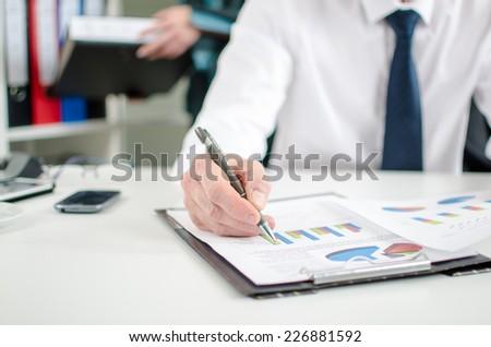 Businessman checking financial charts at office - stock photo